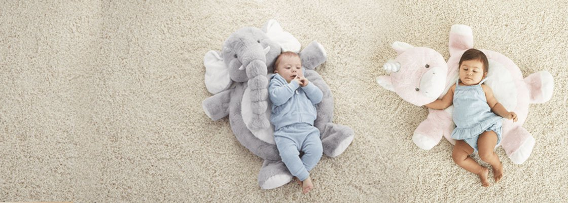 boy baby and girl baby lying on stuffed animal mats on a cream carpet
