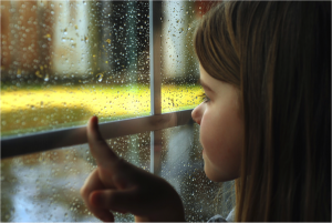 girl by window looking at rainy day