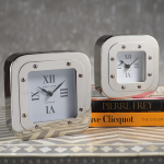 two silver table clocks