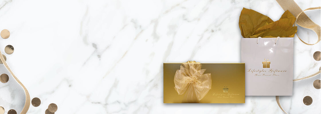 marble background behind two giftwrapped gifts in gold with confetti and ribbons