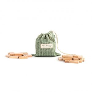 Dominoes piled next to a green cloth bag