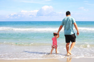 Father and young daughter walking on the beach