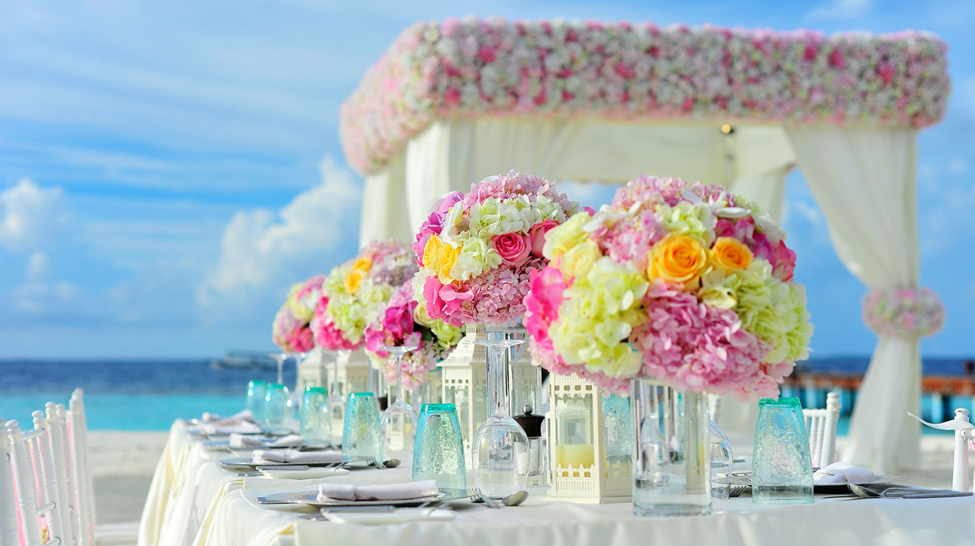 pink,green, and orange flower arrangements on a wedding table at the beach