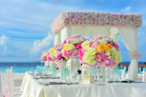 Pink and Yellow Floral Arrangements at a Beach Wedding